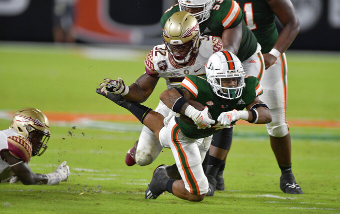 Miami running back Jaylan Knighton dives for an extra yard against Florida State linebacker Stephen Dix, Jr. during the first half of an NCAA college football game, Saturday, Sept. 26, 2020, in Miami Gardens, Fla. (Michael Laughlin/South Florida Sun-Sentinel via AP)