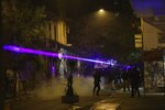 Hooded protesters use an aim laser pointer to riot police during minor clashes in Athens, Friday, Dec. 6, 2019. Thousands of protesters in Greece have joined marches in the nation's capital and other cities to mark the anniversary of the fatal police shooting of a teenager that sparked extensive rioting 11 years ago. (AP Photo/Yorgos Karahalis)