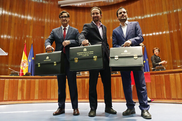 Podemos (United We Can) leader Pablo Iglesias, centre, flanked by new Health Minister Salvador Illa, left and Podemos member Alberto Garzon, minister of consumption pose with their ministerial briefcases in Madrid, Spain, Monday, Jan. 13, 2020. Iglesias will be one of four deputy prime ministers and in charge of social rights and sustainable development after a total of 22 ministers took their oaths in Spain's center to far left-wing coalition administration, a first in a country once dominated by two main parties taking turns in power. (AP Photo/Manu Fernandez)