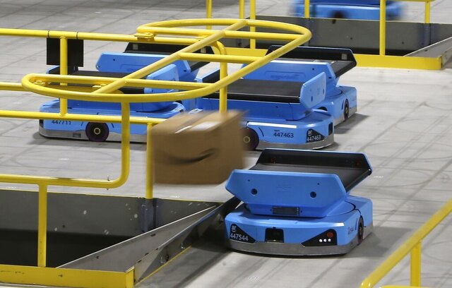 FILE - In this Dec. 17, 2019, file photo an Amazon robot sends a package down a chute, transporting packages from workers to chutes that are organized by zip code, at an Amazon warehouse facility in Goodyear, Ariz. Amazon.com reports financial results on Thursday, Jan. 30, 2020. (AP Photo/Ross D. Franklin, FIle)