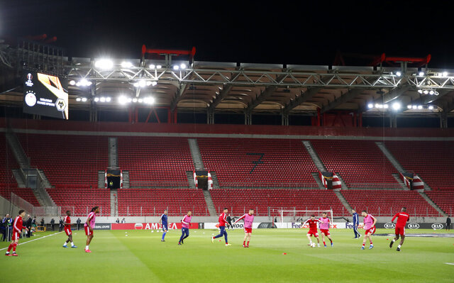 Olympiakos players challenge for the ball during warm up prior the Europa League round of 16 first leg soccer match between Olympiakos and Wolverhampton Wanderers at the Karaiskakis Stadium in Piraeus, Greece, Thursday, March 12, 2020. The match is being played in an empty stadium because of the coronavirus outbreak. (AP Photo/Thanassis Stavrakis)