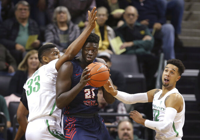 Oregon's Francis Okoro, left, and Anthony Mathis, right, pressure Fresno State's Assane Diouf, center, during the first half an NCAA college basketball game in Eugene, Ore., Tuesday, Nov. 5, 2019. (AP Photo/Chris Pietsch)