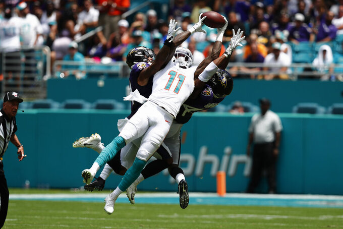 Miami Dolphins wide receiver DeVante Parker (11) holds onto a pass as Baltimore Ravens cornerbacks Anthony Averett (34) Marlon Humphrey (44) defend, during the first half at an NFL football game, Sunday, Sept. 8, 2019, in Miami Gardens, Fla. (AP Photo/Brynn Anderson)