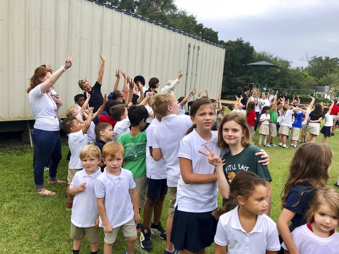 Myrtle Place Elementary students and faculty hold up peace signs toward a drone taking pictures of them from the sky during a ceremony Friday, Sept. 20, 2019, celebrating International Day of Peace as a school in Lafayette, La. The students are standing in the shape of a giant heart and the letter P-A-I-X, which spells the French word for