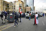 Anti-government protesters block a main highway by garbage containers in Beirut, Lebanon, Friday, Jan. 17, 2020. Protesters closed major roads in the capital Beirut and around wide parts of Lebanon paralyzing the country as the political crisis over the formation of a new government worsens. (AP Photo/Bilal Hussein)
