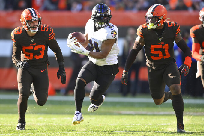Baltimore Ravens running back Mark Ingram (21) rushes after a catch under pressure from Cleveland Browns middle linebacker Joe Schobert (53) and linebacker Mack Wilson (51) during the first half of an NFL football game, Sunday, Dec. 22, 2019, in Cleveland. (AP Photo/David Richard)