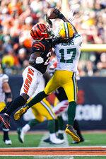 Green Bay Packers wide receiver Davante Adams (17) makes a catch over Cincinnati Bengals cornerback Chidobe Awuzie (22) in the second half of an NFL football game in Cincinnati, Sunday, Oct. 10, 2021. (AP Photo/Bryan Woolston)