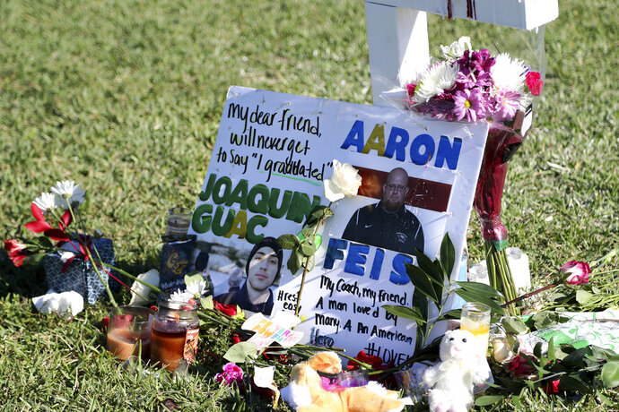 FILE - In this Feb. 16, 2018 file photo, a tribute to student Joaquin Oliver and coach Aaron Feis is left at the base of a white cross at Pine Trails Park in Parkland, Fla. The ESPYs are breaking tradition for this year's Best Coach Award, awarding it posthumously to three Florida high school coaches who died shielding their students from gunfire. Family members of Marjory Stoneman Douglas High School heroes Aaron Feis, Scott Beigel, and Chris Hixon will receive the honor during the award show on July 18 in Los Angeles, the ESPN network announced Wednesday, June 13, 2018.  (Amy Beth Bennett/South Florida Sun-Sentinel via AP, File)