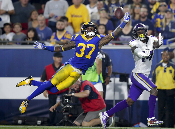 FILE - In this Sept. 27, 2018, file photo, Los Angeles Rams defensive back Sam Shields, left, breaks up a pass intended for Minnesota Vikings wide receiver Stefon Diggs during the first half of an NFL football game in Los Angeles. Shields is one of just four Rams who has played in the Super Bowl before. He finds the privilege even sweeter the second time around. In that big game against Pittsburgh eight years ago, Shields won a ring as an undrafted rookie defensive back making plays for Green Bay. He eventually became a Pro Bowl cornerback for the Packers before a fairly innocuous tackle in the 2016 season opener changed his life. (AP Photo/Jae C. Hong, File)