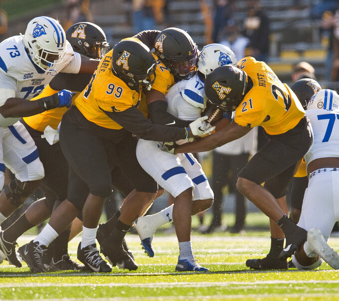 Appalachian State's Jordan Earle (99), D'Marco Jackson (52), and Ryan Huff (21) takedown Georgia State running back Destin Coates in the first half of an NCAA football game, Saturday, Nov. 14, 2020, in Boone, N.C. (Walt Unks/Winston-Salem Journal via AP)