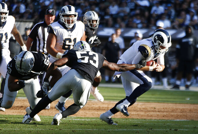 Los Angeles Rams quarterback Brandon Allen, right, evades a tackle by Oakland Raiders' Jason Cabinda (53) during the first half of a preseason NFL football game Saturday, Aug. 10, 2019, in Oakland, Calif. (AP Photo/Rich Pedroncelli)