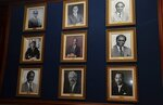 In this June 13, 2019 photo, framed photos of former Bank of Jamaica governors adorn a wall at the bank in Kingston, Jamaica. The central bank focused on using exchange rate adjustments to keep prices of goods and services neither too low nor too high, but that resulted in swings that made it difficult for businesses to plan. The bank now makes monetary decisions based on inflation, seeking a moderate but steady rise in prices.  (AP Photo/Collin Reid)