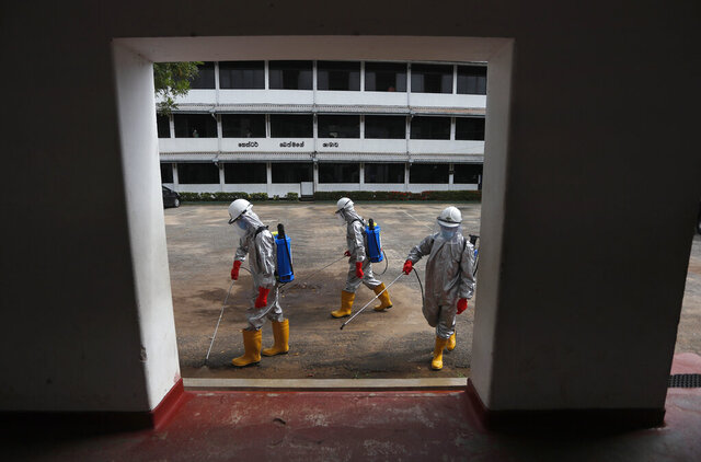 Members of Sri Lanka's St John's ambulance service spray disinfectants in a public school to prevent the spread of coronavirus in Colombo, Sri Lanka, Monday, June 22, 2020. (AP Photo/Eranga Jayawardena)