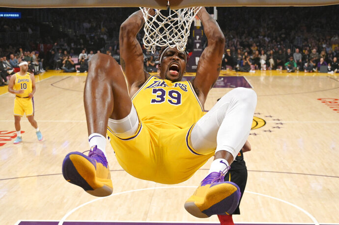 Los Angeles Lakers center Dwight Howard hangs on the basket as he dunks during the first half of an NBA basketball game against the Cleveland Cavaliers Monday, Jan. 13, 2020, in Los Angeles. (AP Photo/Mark J. Terrill)