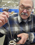In this Monday, Jan. 29, 2018 photo, Henry Marckres, retired maple specialist with the Vermont Agency of Agriculture, tests the sugar concentration of a maple syrup entry at the annual Vermont Farm Show in Essex Junction, Vt. Vermont is the country's largest producer of maple syrup. (AP Photo/Lisa Rathke)
