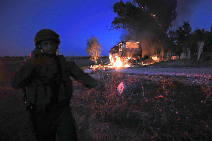 An Israeli soldier stands near a burning bus after it was hit by a mortar shell fired from Gaza near the Israel Gaza border, Monday, Nov. 12, 2018. Israeli media say six people were wounded by Palestinian fire, including a 19-year-old who was critically hurt when a mortar shell hit the bus. (AP Photo/Tsafrir Abayov)