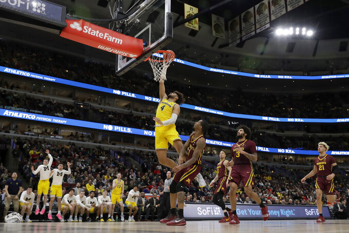 Michigan's Isaiah Livers (4) goes up for a lay up against Minnesota's Dupree McBrayer (1) during the second half of an NCAA college basketball game in the semifinals of the Big Ten Conference tournament, Saturday, March 16, 2019, in Chicago. (AP Photo/Nam Y. Huh)
