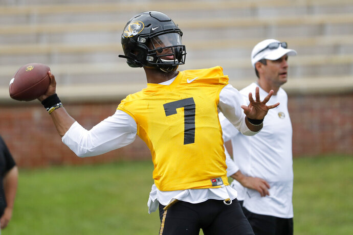 Missouri quarterback Kelly Bryant (7) throws as offensive coordinator Derek Dooley, right, stands off to the side during an NCAA college football practice Monday, Aug. 12, 2019, in Columbia, Mo. (AP Photo/Jeff Roberson)
