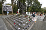 A woman lays flowers at a menorah monument close to a Babi Yar ravine where tens of thousands of Jews were killed during WWII, in Kyiv, Ukraine, Tuesday, Sept. 29, 2020. Photos of victims are seen around the monument. Ukraine marked the 79th anniversary of the 1941 Babi Yar massacre. (AP Photo/Efrem Lukatsky)