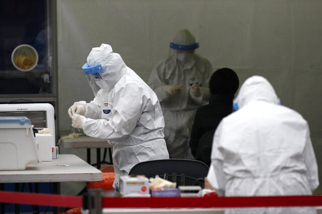 Medical workers wearing protective gears prepare to take sample at a coronavirus testing site in Seoul, South Korea, Wednesday, Dec. 23, 2020. South Korea has added more than 1,000 new coronavirus cases in a resurgence that is erasing hard-won epidemiological gains and eroding public confidence in the government's ability to handle the outbreak. (AP Photo/Lee Jin-man)