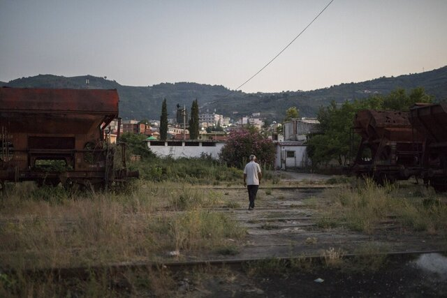 A man takes an evening stroll through an abandoned communist-era train station in the town of Ballsh, Albania, Thursday July 9, 2020. For young people in the rural Albanian town of Ballsh, the best chance of work is to move abroad. But that has been made impossible by the closure of borders as part of the coronavirus response. Nowadays, in this western Albanian town where almost everybody was once employed by an oil refinery that now stands idle, the only thing to do is gather at cafes to chat and wait for better news. (AP Photo/Daniel Cole)