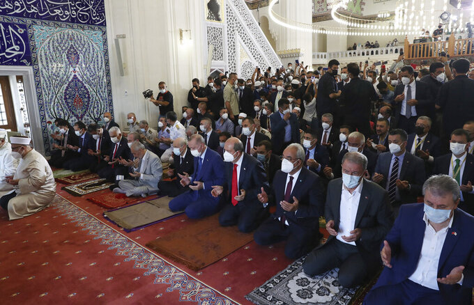 """Turkey's President Recep Tayyip Erdogan, 5th from right, and Turkish Cypriot leader Ersin Tatar, 4th right, perform Eid al-Adha prayers at historical Hala Sultan Mosque, in Nicosia, Cyprus, Tuesday, July 20, 2021. Erdogan said Tuesday his country will talk with the Taliban regarding Turkey's bid to operate and secure the airport in the Afghan capital, Kabul. Speaking after Eid al-Adha prayers, President Erdogan acknowledged that the hardline Islamist group had some """"discomforts"""" over Turkey's proposed plans for Hamid Karzai International Airport.(Turkish Presidency via AP, Pool)"""