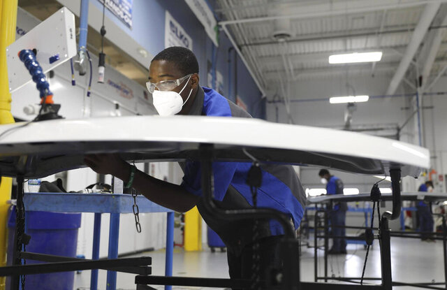 Darius Rindell, wearing a face mask, uses a small specialize bar to push out a dent in a car hood, during a paint-less dent repair class at College of Lake County in Grayslake, Ill., Thursday, July 8, 2020. (Abel Uribe/Chicago Tribune via AP)