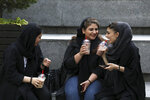 In this Tuesday, July 2, 2019 photo, youngsters spend an afternoon while siting on steps outside a shopping mall in northern Tehran, Iran.  A few daring women in Iran's capital have been taking off their mandatory headscarves, or hijabs, in public, risking arrest and drawing the ire of hard-liners. Many others stop short of outright defiance and opt for loosely draped scarves that show as much hair as they cover. More women are pushing back against the dress code imposed after the 1979 Islamic Revolution, and activists say rebelling against the hijab is the most visible form of anti-government protest in Iran today.  (AP Photo/Vahid Salemi)