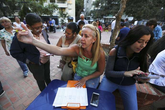 In this Feb. 19. 2019 photo, people fill forms to joint to the group of volunteers that will help to introduce humanitarian aid into Venezuela, during a meeting to recruit volunteers, at a square in Caracas, Venezuela. The opposition expects to mobilize on Saturday. (AP Photo/Fernando Llano)