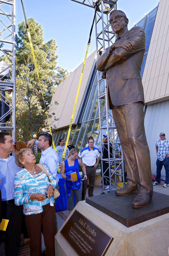 FILE - In this Oct. 26, 2012, file photo, Nan Wooden looks at a statue of her late father, UCLA men's basketball coach John Wooden, after its unveiling outside the new Pauley Pavilion at UCLA in Los Angeles. Nan Wooden died Tuesday, Sept. 14, 2021. She was 87. The school said she died of natural causes at a care facility in the San Fernando Valley, according to family members. She had suffered a series of strokes in recent years. (AP Photo/Mark J. Terrill, File)