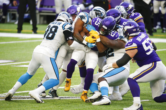 Minnesota Vikings running back Alexander Mattison (25) is tackled by Carolina Panthers defenders during the second half of an NFL football game, Sunday, Nov. 29, 2020, in Minneapolis. (AP Photo/Bruce Kluckhohn)