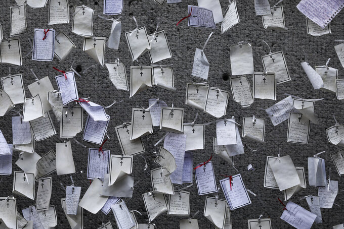 FILE - In this April 14, 2021, file photo, messages written by loved ones and dedicated to the deceased hang from a wall at a memorial for COVID-19 victims installed outside the Basilica of Guadalupe in Mexico City. The global death toll from the coronavirus topped a staggering 3 million people Saturday, April 17, 2021, amid repeated setbacks in the worldwide vaccination campaign. (AP Photo/Eduardo Verdugo, File)