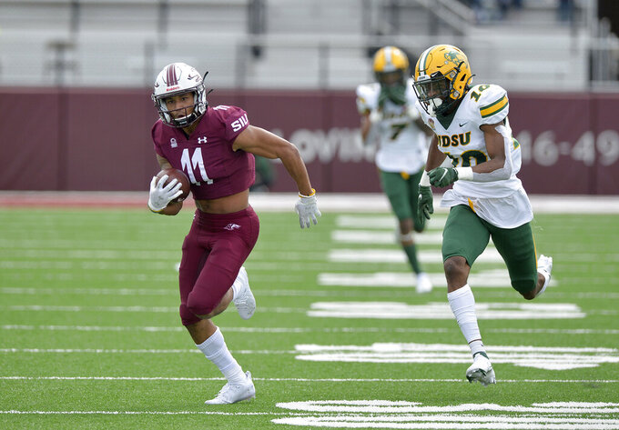 Southern Illinois wide receiver Avante Cox (11) sprints away from North Dakota State safety Dom Jones (10) on a 65-yard reception during the second quarter of an NCAA college football game Saturday, Feb. 29, 2021, in Carbondale, Ill. (Byron Hetzler/The Southern Illinoisan via AP)