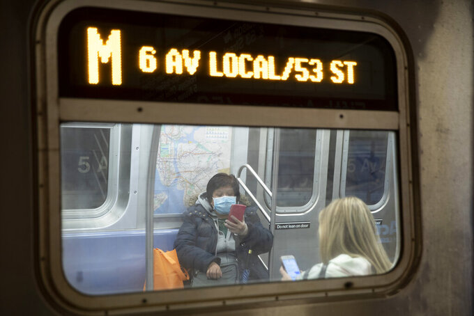 FILE- In this March 19, 2020 file photo, a commuter wears a face mask while riding the subway in New York. Commuters who refuse to wear a mask on New York City subways, trains and buses could be fined $50 starting Monday, Sept. 14, 2020. (AP Photo/Mary Altaffer, File)