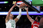 Boston Celtics center Enes Kanter (11) dunks next to Detroit Pistons guard Sviatoslav Mykhailiuk (19) during the first half of an NBA basketball game in Boston, Wednesday, Jan. 15, 2020. (AP Photo/Charles Krupa)