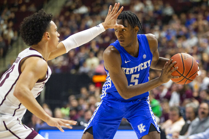 Kentucky guard Immanuel Quickley (5) looks to pass the ball as Texas A&M guard Andre Gordon (20) defends during the first half of an NCAA college basketball game Tuesday, Feb. 25, 2020, in College Station, Texas. (AP Photo/Sam Craft)