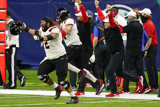 Ball State players run onto the field after the team defeated Buffalo in the Mid-American Conference championship NCAA college football game, Friday, Dec. 18, 2020, in Detroit. (AP Photo/Carlos Osorio)