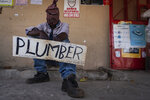 An unemployed plumber advertises for work in Lenasia South, Johannesburg, Wednesday, Oct. 28, 2020. More than 2 million jobs have been lost during the economic downturn caused by the pandemic in South Africa, a country of 60 million people.(AP Photo/Shiraaz Mohamed)