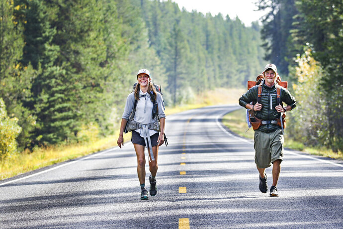 Peter Weinberger, 33, of Massachusetts, and Sarah Williams, 29, of Kalispell, Mont., walk north along Camas Creek Road in Glacier National Park, Mont., on Sept. 23, 2020, during the last leg of their journey on the Continental Divide Trail. The route leads from the Mexican border to the Canadian Border. (Hunter D'Antuono/Flathead Beacon via AP)