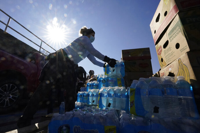 Volunteers load water for people at a San Antonio Food Bank drive-through food distribution site held at Rackspace Technology, Friday, Feb. 19, 2021, in San Antonio. (AP Photo/Eric Gay)