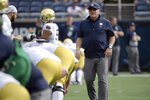 FILE - In this Saturday, Dec. 28, 2019, file photo, Notre Dame head coach Brian Kelly, right, watches warmups before the Camping World Bowl NCAA college football game against Iowa State in Orlando, Fla. Normally, in March, college football teams all over the country would be preparing for the upcoming season. That's gone now, because of the new coronavirus pandemic, and coaches are trying to figure out how to recreate some of what has been lost. (AP Photo/Phelan M. Ebenhack, File)