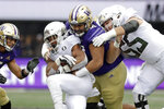 Washington's Tuli Letuligasenoa, center, tackles CJ Verdell as Oregon's Jake Hanson, right, moves in behind in the first half of an NCAA college football game Saturday, Oct. 19, 2019, in Seattle. (AP Photo/Elaine Thompson)