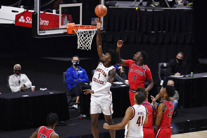 Boston College's CJ Felder goes up for a basket as St. John's Greg Williams Jr., right, defends in the first half of an NCAA college basketball game, Monday, Nov. 30, 2020, in Uncasville, Conn. (AP Photo/Jessica Hill)