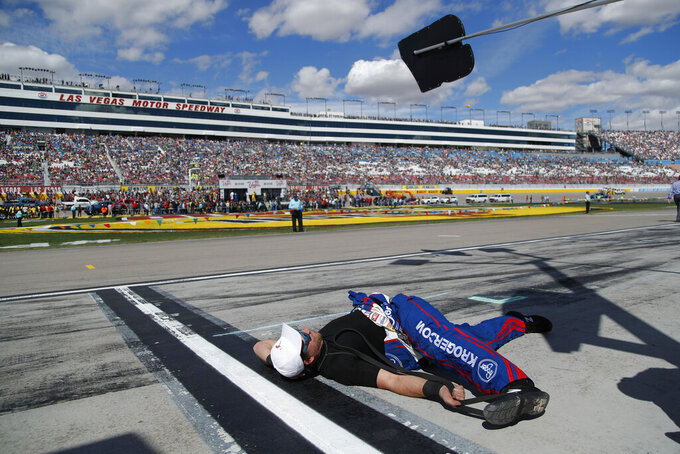 A member of Chris Buescher's pit crew stretches before a NASCAR Cup Series auto race at Las Vegas Motor Speedway, Sunday, March 3, 2019, in Las Vegas. (AP Photo/John Locher)