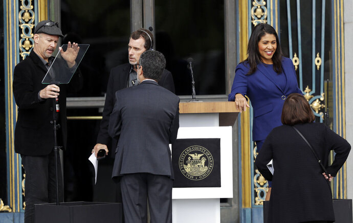 London Breed, top right, talks with staff before being sworn in as San Francisco's new mayor outside City Hall Wednesday, July 11, 2018, in San Francisco. Breed becomes the city's first African American female mayor and she inherits a San Francisco battling homelessness, open drug use and unbearably high housing costs. (AP Photo/Marcio Jose Sanchez)