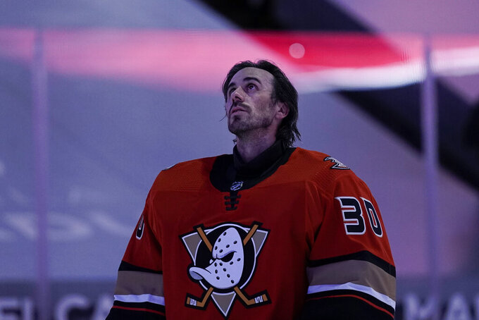 Anaheim Ducks goaltender Ryan Miller listens to the national anthem before the team's NHL hockey game against the Los Angeles Kings, Saturday, May 1, 2021, in Anaheim, Calif. Miller will retire at the conclusion of the season, ending the 18-year career of the winningest American-born goaltender in NHL history. (AP Photo/Jae C. Hong)