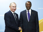 Russian President Vladimir Putin, left, and Guinea's President Alpha Conde pose for a photo during their meeting on the sideline of the Russia-Africa summit in the Black Sea resort of Sochi, Russia, Thursday, Oct. 24, 2019. (Valery Sharifulin, TASS News Agency Pool Photo via AP)