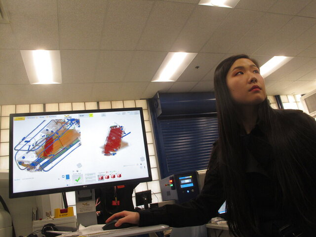 In this Dec. 12, 2019 photo, Bijia Chen, an engineer with a technology company that won a federal contest to find new or better ways to scan incoming mail for illegal opioid shipments, demonstrates how the computer analysis works at a demonstration in Egg Harbor Township, N.J. (AP Photo/Wayne Parry)