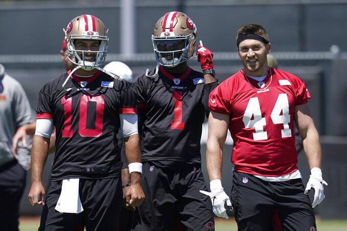 San Francisco 49ers quarterback Jimmy Garoppolo (10) smiles next to quarterback Josh Johnson (1) and fullback Kyle Juszczyk (44) at the team's NFL football training facility in Santa Clara, Calif., Tuesday, May 25, 2021. (AP Photo/Jeff Chiu)