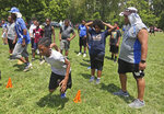 In a June 29, 2019 photo, Michael Whitlow, right, watches a football practice in Helsel Parkin Columbus. Michael and his wife Maree are founders of the Columbus Inspiring Children to Excellence football program.   (Doral Chenoweth III/The Columbus Dispatch via AP)